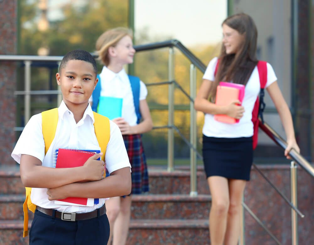 middle school preteens in school uniforms with backpacks