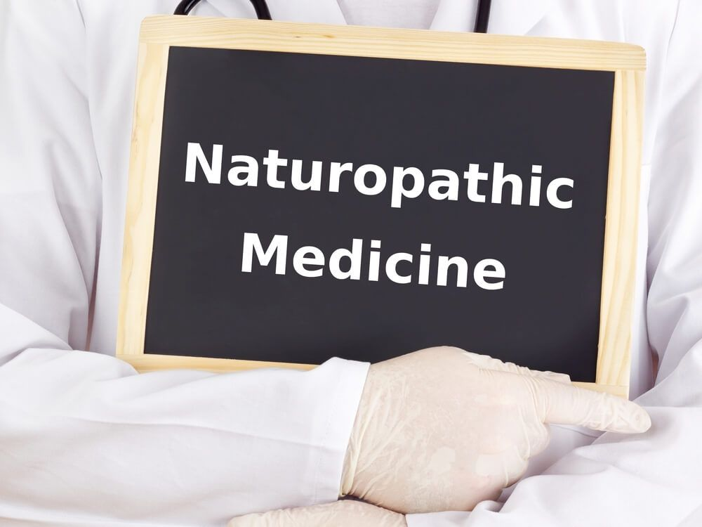 Doctor holds naturopathic medicine sign